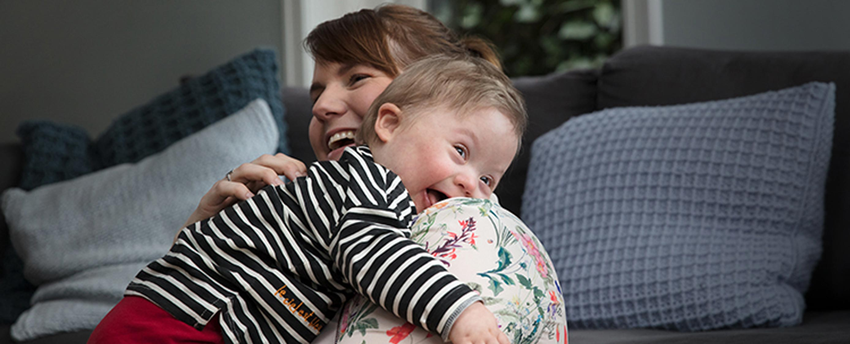 Mother Hugging a Smiling Baby on a Sofa