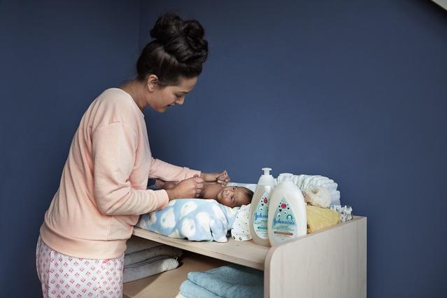 Baby next to Johnson's® newborn skin care products
