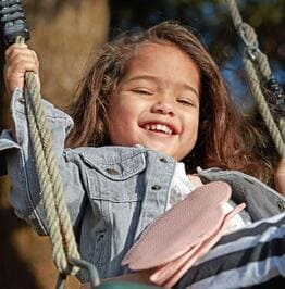 Laughing Toddler Playing on a Tree Swing